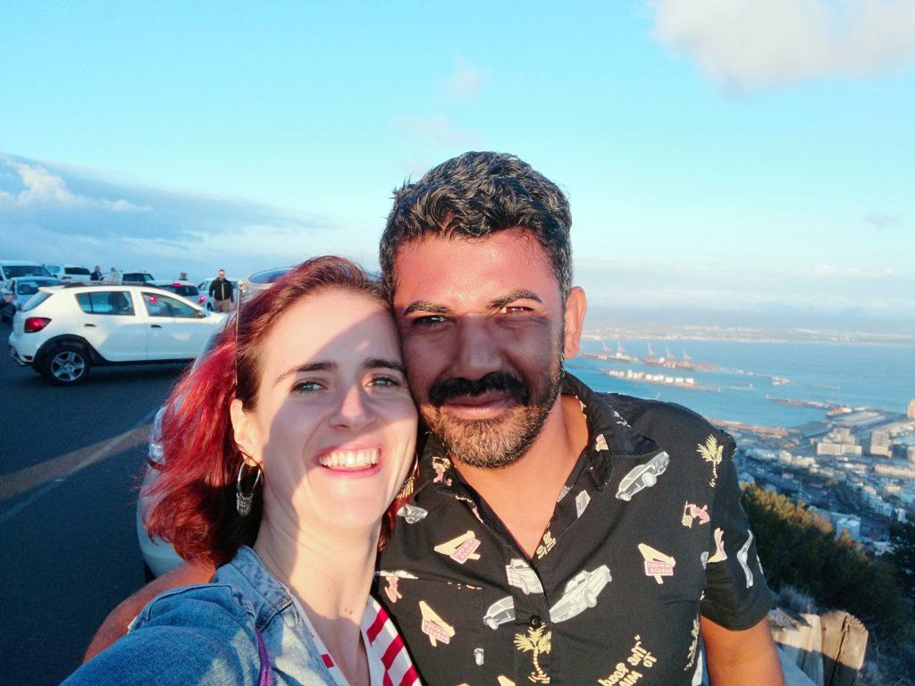 Frau und Mann lächeln in die Kamera, dahinter sieht man das Meer und eine Stadt.