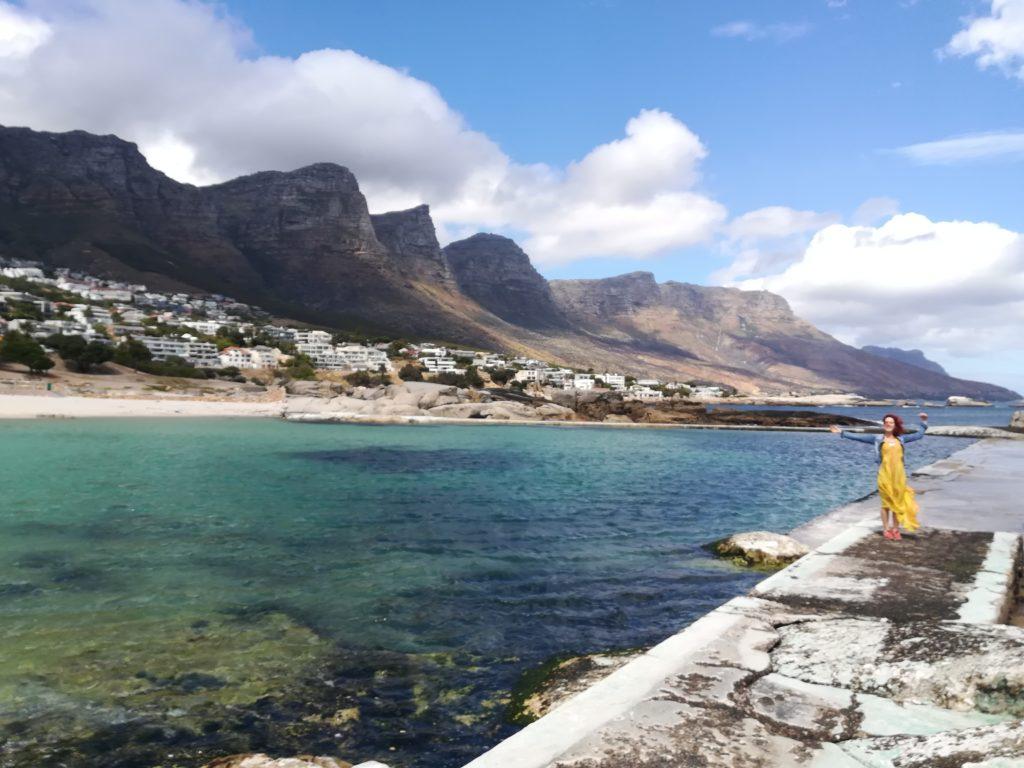 Berge, türkisblaues Wasser und eine Frau mit gelbem Kleid im Vordergrund