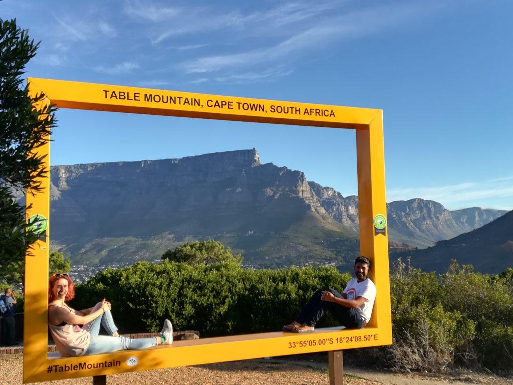 Zwei Menschen sitzen in einem gelben Rahmen, hinter ihm ist der Tafelberg von Kapstadt zu sehen