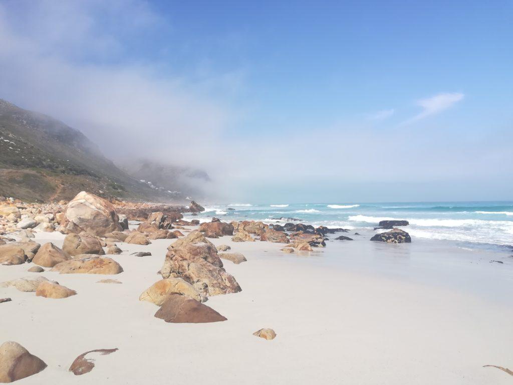 Eine Landschaft - blaues Meer, weißer Strand und braune Felsen